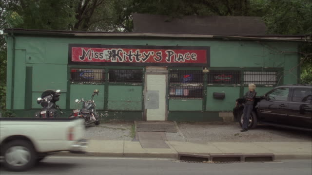 wide angle of bar with sign for miss kitty's place. two motorcycles parked in front. lower class.