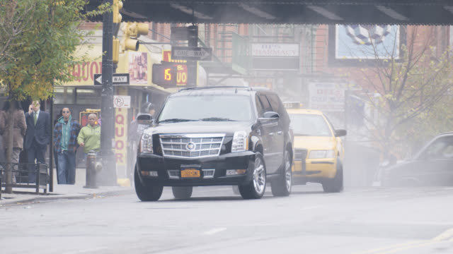 stockvideo's en b-roll-footage met wide angle of black suv driving on city street. suv passes under bridge or overpass and parks. pedestrians visible. taxis visible. - sports utility vehicle