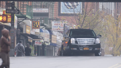 vídeos y material grabado en eventos de stock de wide angle of black suv driving on city street. suv passes under bridge or overpass and parks. pedestrians visible. taxis visible. - sports utility vehicle