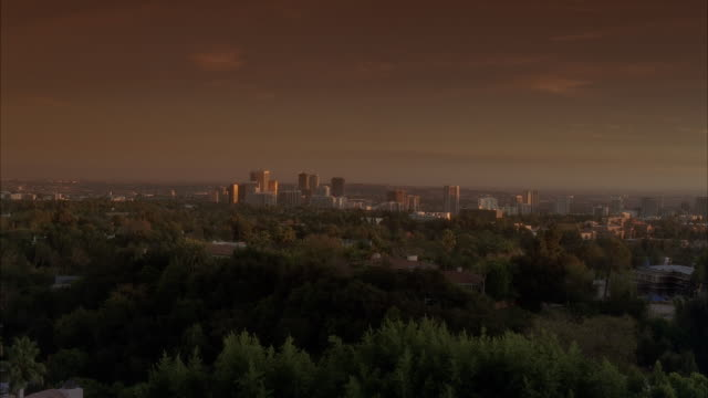 wide angle of city and skyline from mountain or hill. trees or woods visible in fg. could be century city. mountains visible in bg. - hill stock videos & royalty-free footage