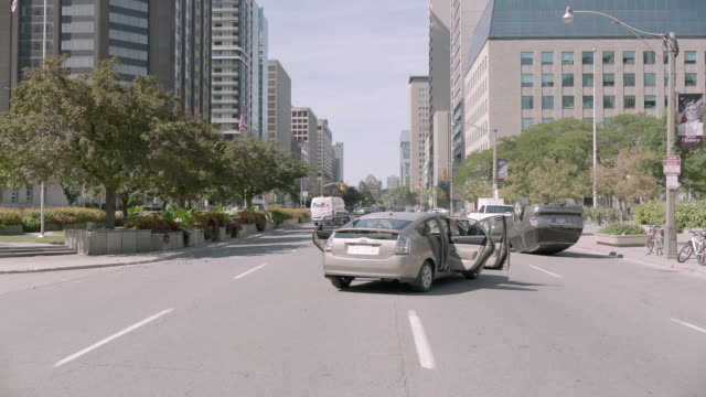 wide angle of city street. abandoned and overturned cars visbile. office buildings. smoke rises from street. could be attack, emergency, invasion, or natural disaster. - abandoned stock videos and b-roll footage