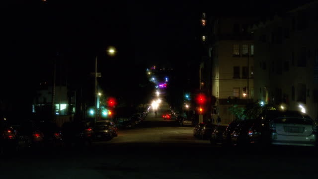 stockvideo's en b-roll-footage met wide angle of city street at night as cars move from fg to bg. neon signs visible on main street in bg. could be bar or nightclub. could be hollywood. apartment buildings line street. - bar gebouw