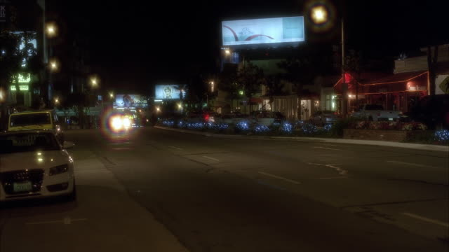 wide angle of convertible car driving on sunset boulevard past shops, restaurants, and storefronts. billboards and advertisement visible. could be sunset strip, west hollywood. - west hollywood stock videos & royalty-free footage