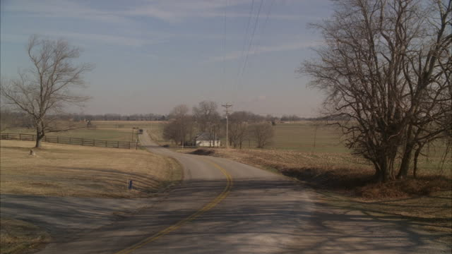 wide angle of country road. telephone poles and wires visible. fences. countryside or farmland. tour bus and van drive by on road from bg to fg. - telegraph pole stock videos and b-roll footage