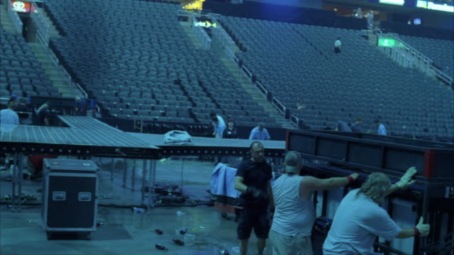wide angle of crew and maintenance men and women cleaning up stadium, convention center, or auditorium after concert. sweeping and taking down stage equipment.