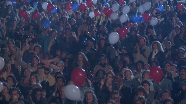 wide angle of crowd standing and cheering. see military planes  on display in background. see people holding red, white and blue balloons. see mariens holding flags at end while audience begins to sing national anthem.