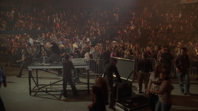 wide angle of crowds, spectators, or audience at concert or convention center. crew visible setting up equipment in fg. barricades visible. people wearing cowboy hats clap and cheer. could be country music concert. - country music stock videos and b-roll footage