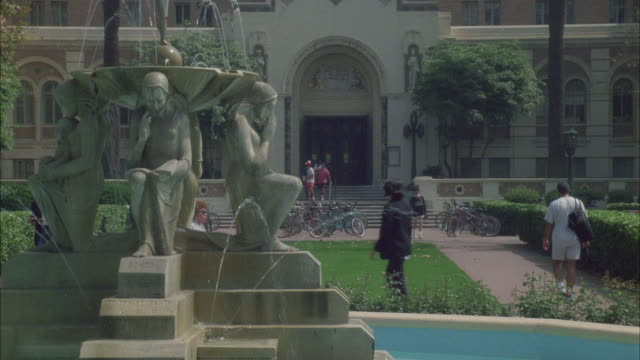 wide angle of doheny library at the university of southern california, usc. youth triumphant or the four cornerstones of democracy fountain. brick buildings. college campuses, private schools. courtyards.
