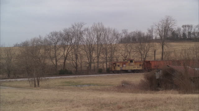 vidéos et rushes de wide angle of dry grass in meadows, countryside or rural area. freight train on railroad tracks. bare branches on trees. - tennessee