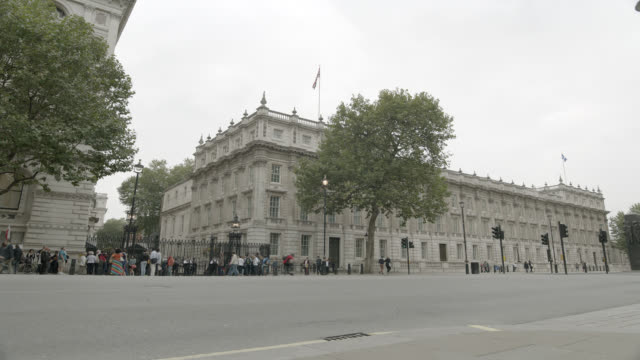 wide angle of entrance to 10 downing street and government buildings. whitehall sw1. pedestrians and tourists visible. women of world war ii monumnet or memorial partially visible. - 10 downing street stock videos and b-roll footage