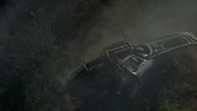 wide angle of foggy hillside with small trees, bushes and shrubs. sports car, could be 1964 chevrolet corvette sting ray, falling down hill, flips  several times before stopping. car parts become detached. car crash. car stunt. dust, smoke, debris. 60 fps
