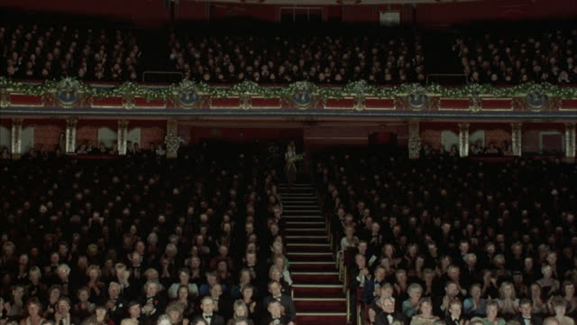 wide angle of formally dressed audience in large theater. - applaudire video stock e b–roll