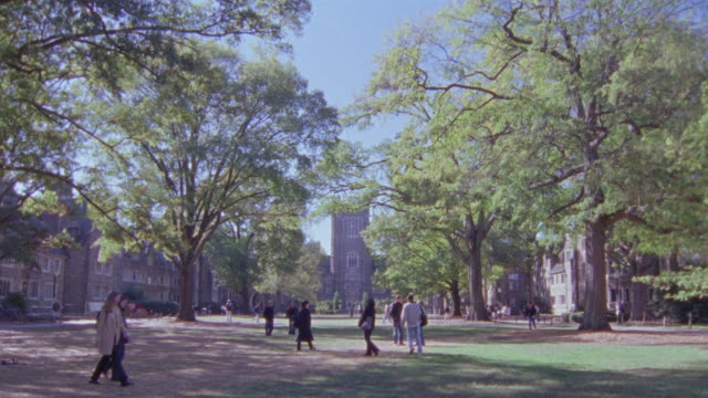 vidéos et rushes de wide angle of grass lawn, quad or commons. trees. students walking. stone buildings in bg. college campus. duke university. - campus
