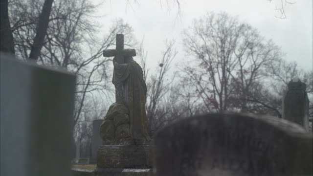 wide angle of gravestones and headstones in graveyard or cemetery. statues. overcast.