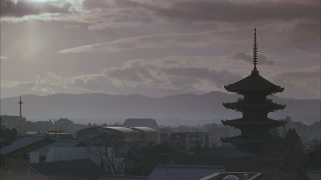 Wide angle of Japanese city Kyoto. Multi-story pagoda on right side amid many houses and other buildings. Could be temple or shrine. Mountains in background and sun is shining through clouds in sky.