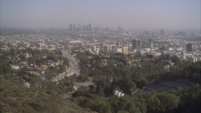 Wide angle of los angeles and hollywood city skylines. skyscrapers and high rise office or apartment buildings of downtown skyline in bg. pov from hollywood hills or mountain.