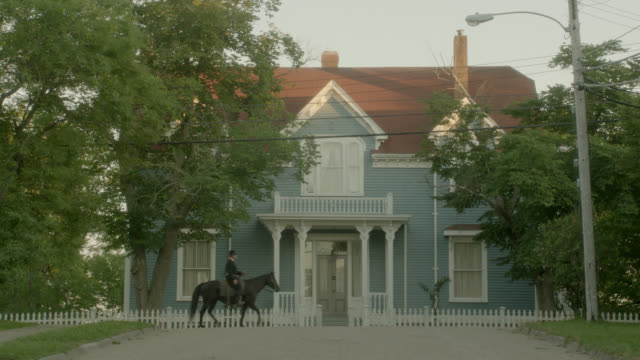 wide angle of multi-story house in residential areas. trees visible. man rides horse past house from left to right. white picket fence in front of house.