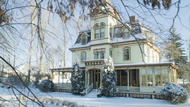 vídeos y material grabado en eventos de stock de wide angle of mult-story snow covered victorian house. trees and branches visible. - estilo victoriano