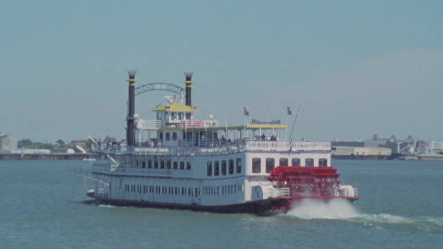 wide angle of riverboat or ferry on river. camera zooms out and zooms back to riverboat. could be tour boat. see piers in background. paddlewheelers. mississippi river. - steam liner stock videos & royalty-free footage