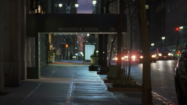 wide angle of sidewalk and city street in front of office building, hotel, or apartment building. awning over entrance to building reads woodstock tower. - awning stock videos and b-roll footage