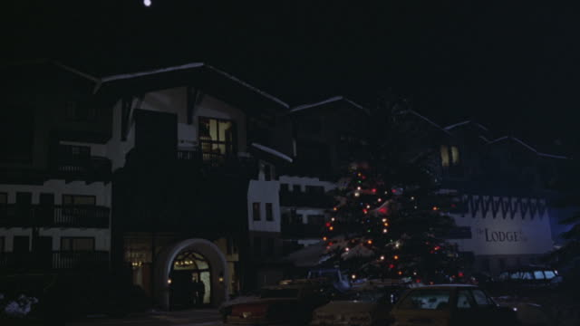 wide angle of ski resort. see sign that says the lodge in front. christmas tree in front of lodge lit up. front driveway. - ski lodge stock videos & royalty-free footage