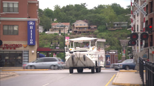 Wide angle of small town area of Branson, Missouri. cars, suv's, amphibious tourist boat driving slowly over railroad crossing and through local streets. crossing signals, Hilton Hotel, emergency vehicle, and parking lot visible. tourists in boat wave.