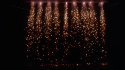vídeos y material grabado en eventos de stock de wide angle of sparks falling from lights in ceiling. could be stage or performance. pyrotechnic effect. - auditorio