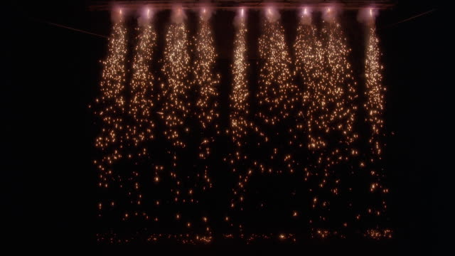 stockvideo's en b-roll-footage met wide angle of sparks falling from lights in ceiling. could be stage or performance. pyrotechnic effect. - toneel