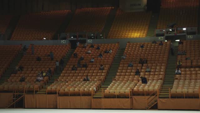 wide angle of stadium, auditorium, or concert venue. the forum. people visible on stairs while others sit. - zuschauerraum stock-videos und b-roll-filmmaterial