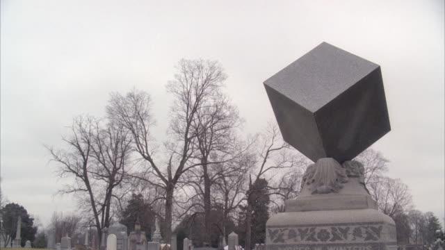 vídeos de stock, filmes e b-roll de wide angle of stone cube statue, gravestone or memorial. graveyard, cemetery. bare branches on trees. overcast sky. - estátua