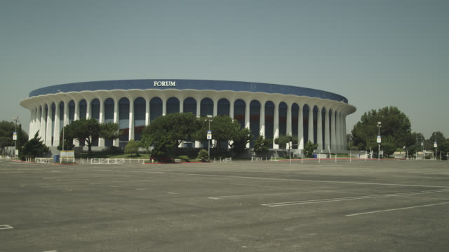 wide angle of the forum stadium or arena. parking lot partially visible. - inglewood video stock e b–roll