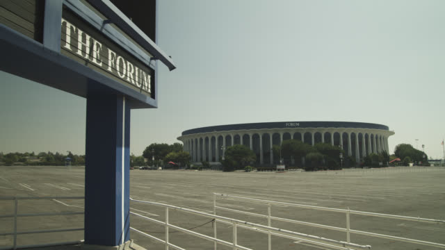 wide angle of the forum stadium. sign partially visible in fg. empty parking lot. - inglewood video stock e b–roll