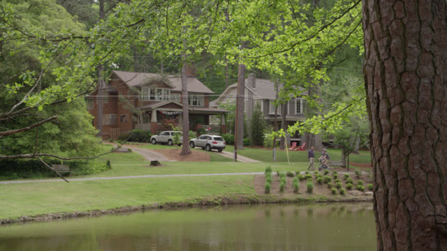 wide angle of two story upper middle class houses. pond in fg. - bicycle parking station stock videos and b-roll footage