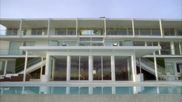 wide angle of upper class mansion or house. multi-story with many windows and balconies. swimming pool and outdoor lounge area visible.
