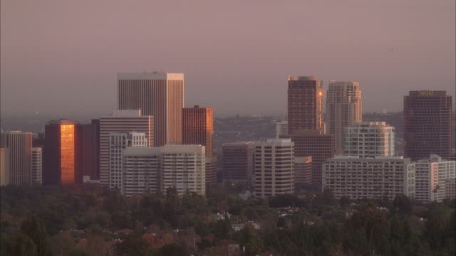 wide angle of westwood and century city skyline at sunset. high rise office buildings, conditions, hotels, and apartment buildings. trees and houses in fg. - century city stock-videos und b-roll-filmmaterial