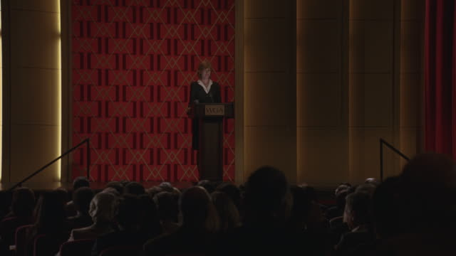wide angle of woman at podium on stage in large auditorium or with gold and red accents. podium reads - podio video stock e b–roll