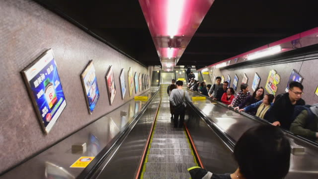 wide angle: people on an escalator in a hong kong subway - bahngleis stock-videos und b-roll-filmmaterial