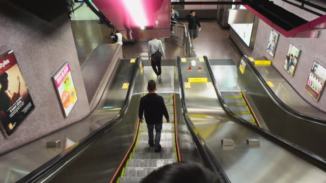 wide angle: people riding down on an escalator in a subway - escalator stock videos & royalty-free footage