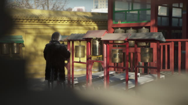 wide angle: people spin prayer wheels while walking through a mongolian plaza - ulaanbaatar, mongolia - independent mongolia stock videos & royalty-free footage