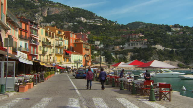 wide angle: people walking by buildings and harbor - france stock videos & royalty-free footage