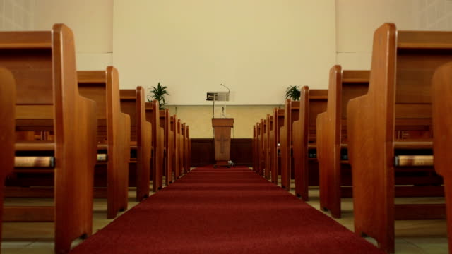 wide angle push-in of church pews and pulpit - kanzel stock-videos und b-roll-filmmaterial