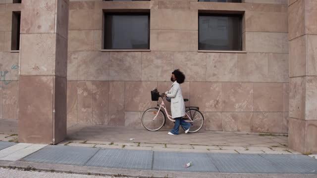 scatto grandangolare di una donna d'affari che si sposta per lavorare con una bici - video al rallentatore - zona pedonale strada transitabile video stock e b–roll