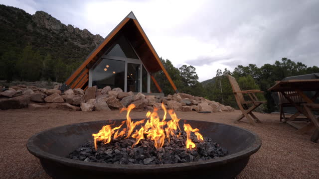 wide angle shot of a cast iron gas fire pit in front of a modern xeriscaped tiny home in western colorado - modern rock stock videos & royalty-free footage