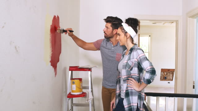 wide angle shot of a couple talking about paint colors for their home. - home improvement stock videos & royalty-free footage