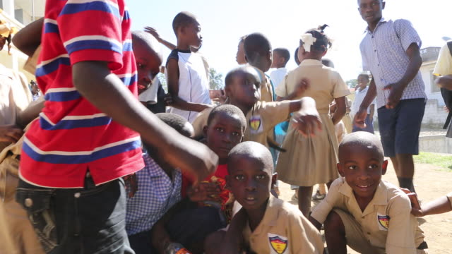 a wide angle shot of a group of primaryschool pupils on a schoolyard in pilate haiti a teacher is joining and is gathering the group of primaryschool... - afro caribbean ethnicity stock videos and b-roll footage