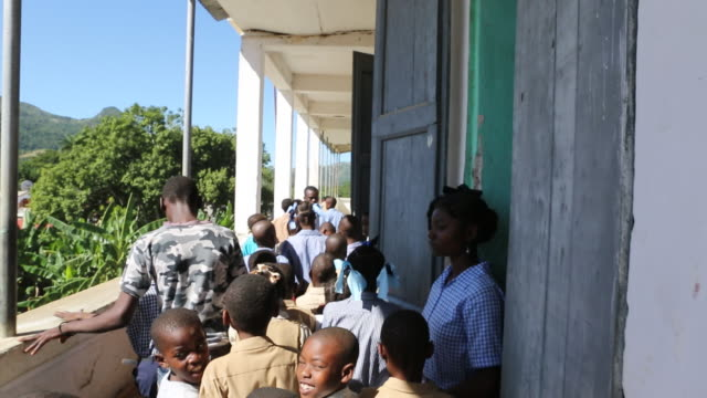 a wide angle shot of a group of primaryschool pupils on the way in their classroom on a corridor of a school building in pilate haiti - hispaniola stock videos and b-roll footage