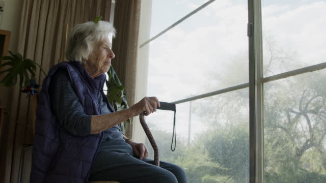 wide angle shot of a happy, comfortable elderly senior caucasian woman indoors looking out the window in the summer - retirement community stock videos & royalty-free footage