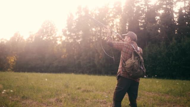 stockvideo's en b-roll-footage met groothoek schot van een jager shooting shotgun (slow motion) - vogeljacht