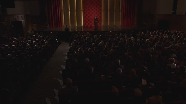 a wide angle shot of a person standing on the stage in an auditorium. - auditorium stock videos & royalty-free footage