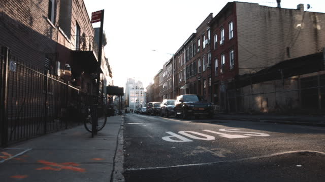 vídeos de stock, filmes e b-roll de wide angle shot of a quiet block in brooklyn at sunrise - plano geral ponto de vista